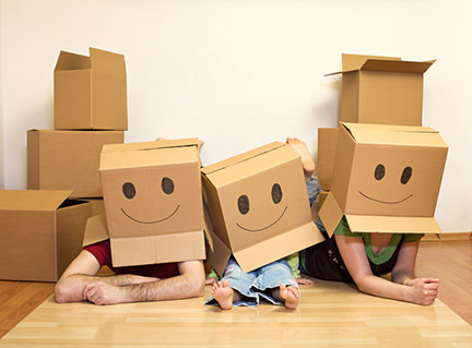 Man, woman and little girl with smiley face cardboard boxes on their heads