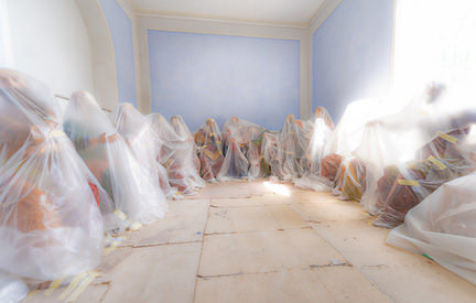 bubble wrapped mannequins sitting on the floor in an empty room