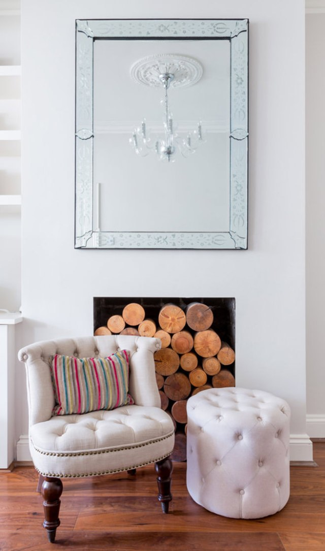 Buttoned chair & footstool in front of a fireplace filled with logs with large mirror above