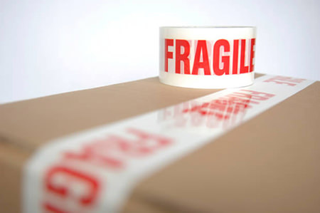 Cardboard box with red & white fragile packing tape