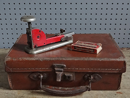 small vintage leather suitcase and industrial stapler with staples