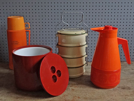 selection of vintage picnic items including a two-tone orange Thermos vacuum flask, orange vacuum jug, maroon Crayonne ice bucket and cream enamel tiffin