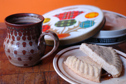 plate of shortbread tails with mug of tea and vintage shortbread tin
