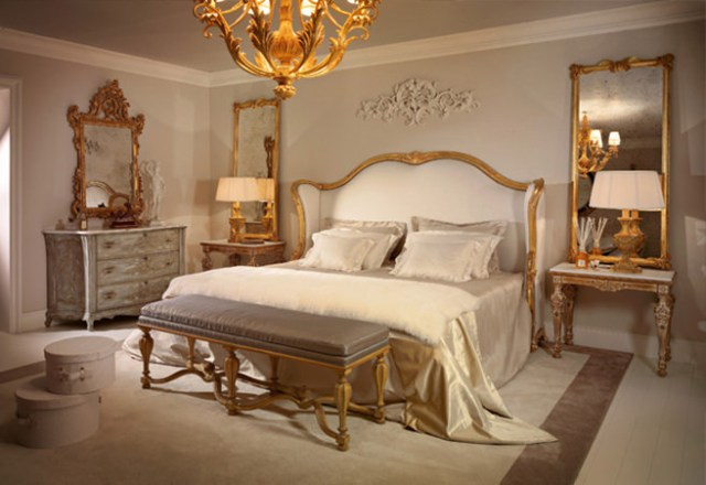 Luxe bedroom with gilt chandelier, mirrors and furniture