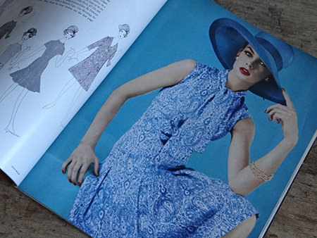 Model wearing a blue dress and hat in Vogue Magazine, February 1962