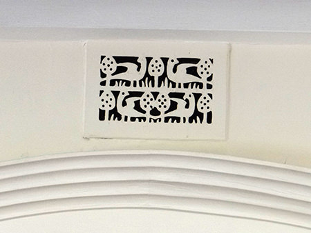 Arts & Crafts decorative fireplace vent grille featuring birds and trees