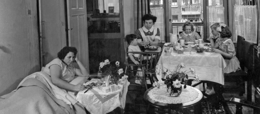 Gezinsverzorgster aan het werk bij een gezin. Moeder ligt in bed, de hulp zit met de kinderen aan tafel voor de broodmaaltijd. (Nationaal Archief/ Spaarnestad)