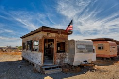 A tattered flag still flies proudly over a long abandoned trailer in Bombay Beach