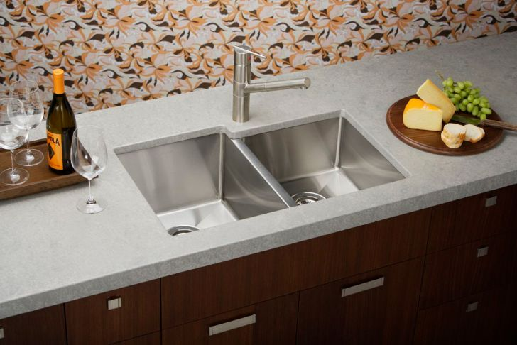 double stainless steel sinks with single stainless steel faucet three wine glasses a bottle of winea a plate of fresh foods expensive gray granite countertop with under cabinetry units fabricated vinyl floor