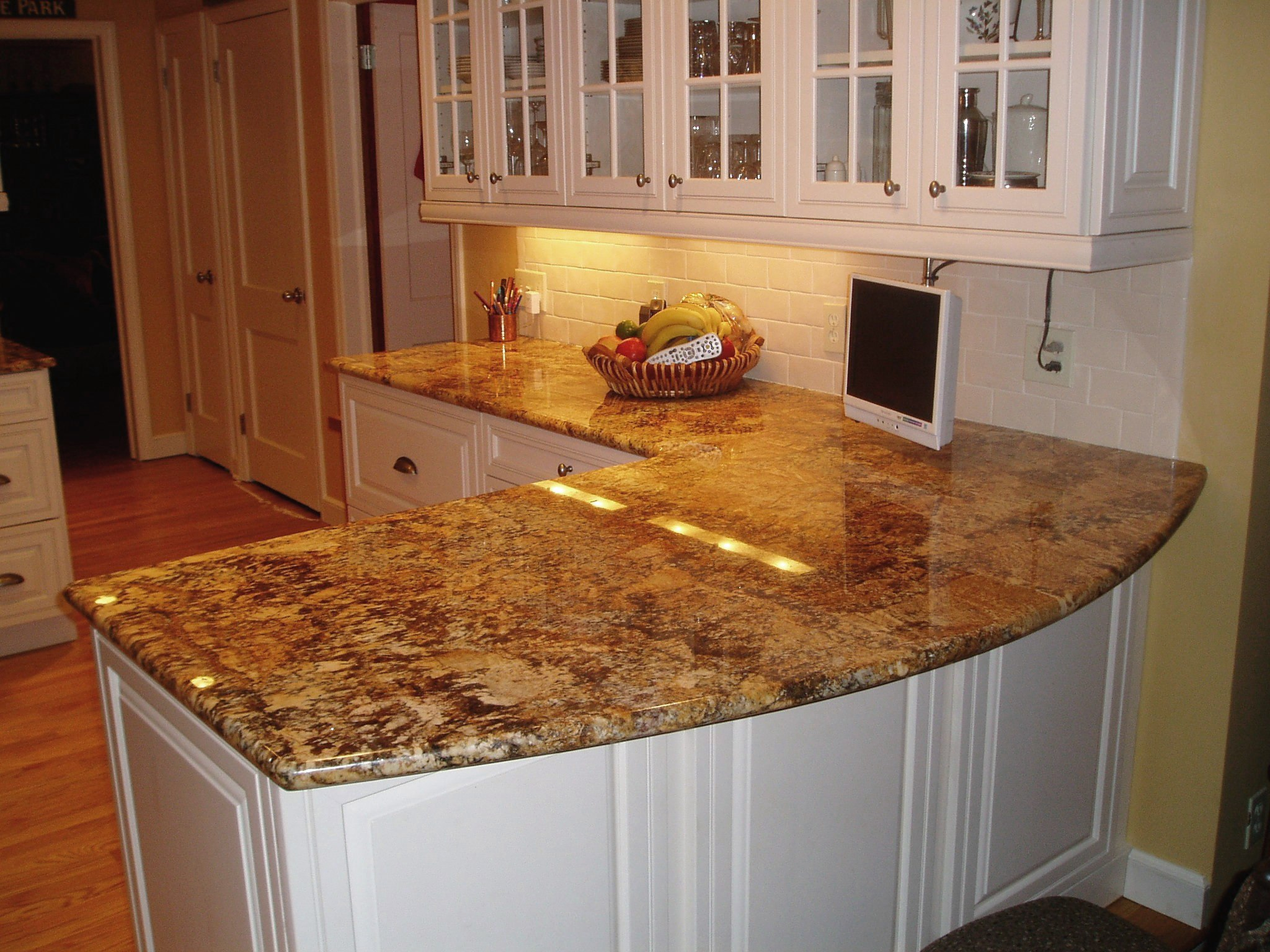 glossy granite countertop with L letter shape a high tech monitor crafted rattan fruits basket top glass door cabinetry