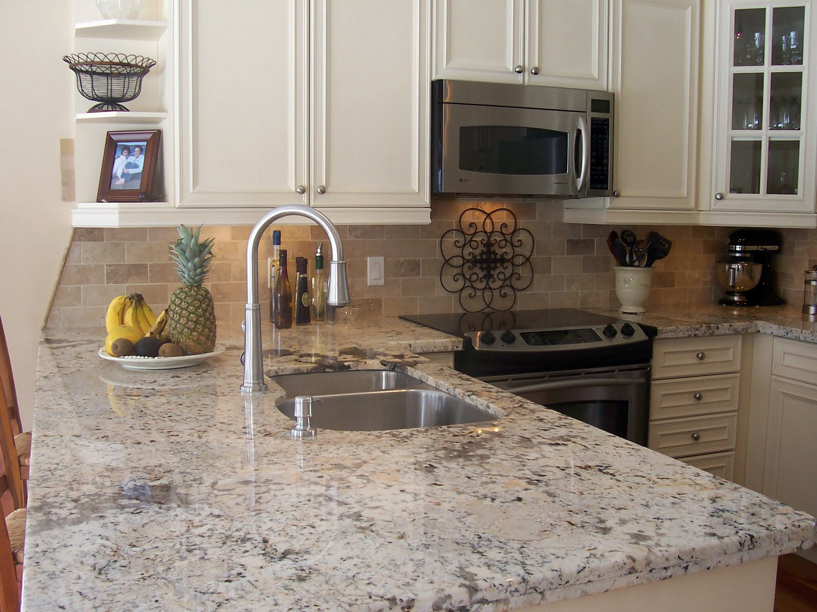 luxurious kitchen set with white dominant cashmere granite for top kitchen island double sinks with a single stainless steel faucet a dish of fuits some modern kitchen appliances