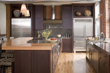 wood surface kitchen island with storage and barstools glossy surface kitchen countertop with sink and faucet wood floors red brick wall system dark stained wood cabinets sliver door refrigerator