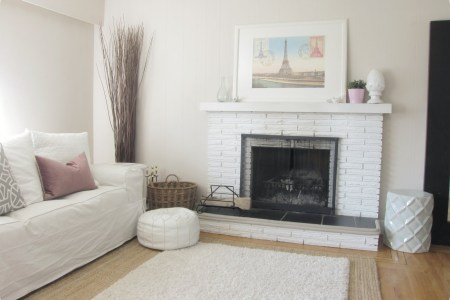 winter mood nicole miller home decor with white painted wall and white couch and fireplace and area rug and wooden floor