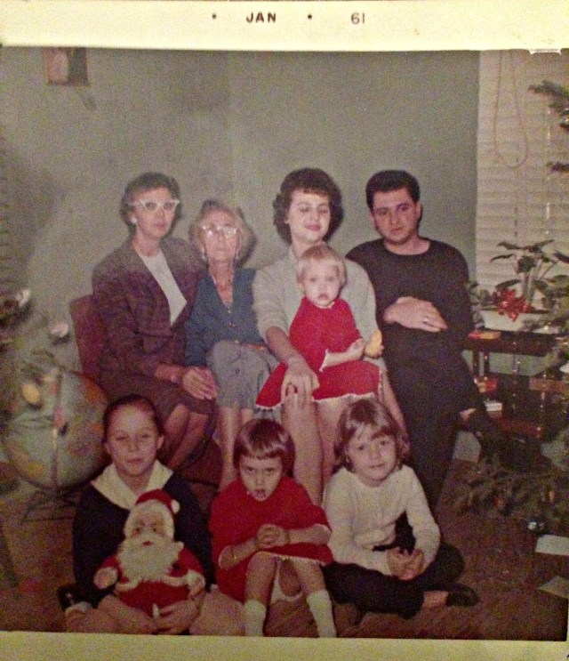 "Top Row from left to right: My great-grandmother Nancy Herring, ""Big Mama"", my Grandma Jackie with my mom on her lap, and my Grandpa Joy. My Aunt Debbie is on the floor in the red dress!"