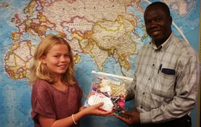 Every little thing makes a difference. Even this zip-locking plastic bag will be a blessing to the family that receives it. Pictured: Paige presenting a Christmas Gift Bag to Pastor Louinet of Haiti.