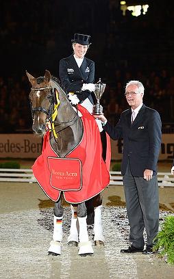 FEI Director of Dressage, Trond Asmyr, presents the Reem Acra Trophy to Germany's Helen Langehanenberg.