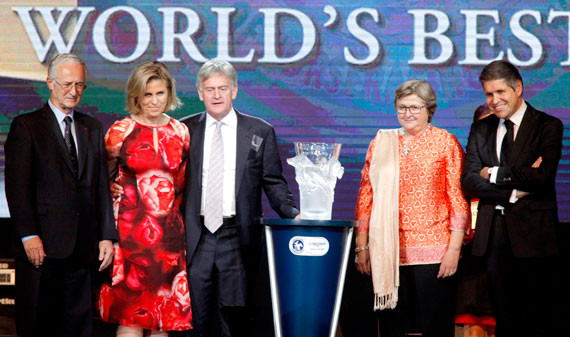 IFHA chairman Louis Romanet, left, and Longines vice-preisdent Juan-Carlos Capelli, right, present a trophy and a Longines watch to Neil Werrett and Lena Attebo representing Black Caviar, and to Criquette Head-Maarek, trainer of Treve, the joint top ranked racehorses.