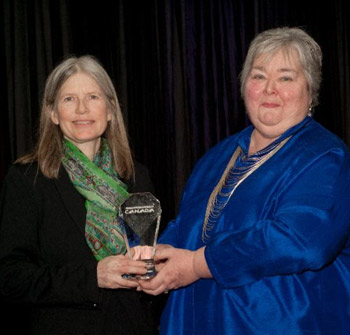 Whitemud Equine Learning Centre Association manager Lynda Tennessen with Equine Canada's Horse Horse Stewardship Award, presented by Jan Stephens.