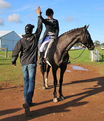Team coach Clarke Johnstone congratulates Sarah Young for her ride on Regal Romar at the Melbourne International Horse Trials in Werribee today.