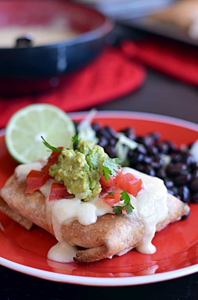 Baked Chicken Chimichangas with Monterey Jack Cheese Sauce.  These are so easy and a new family favorite!  They freeze and reheat well, too! | hostthetoast.com