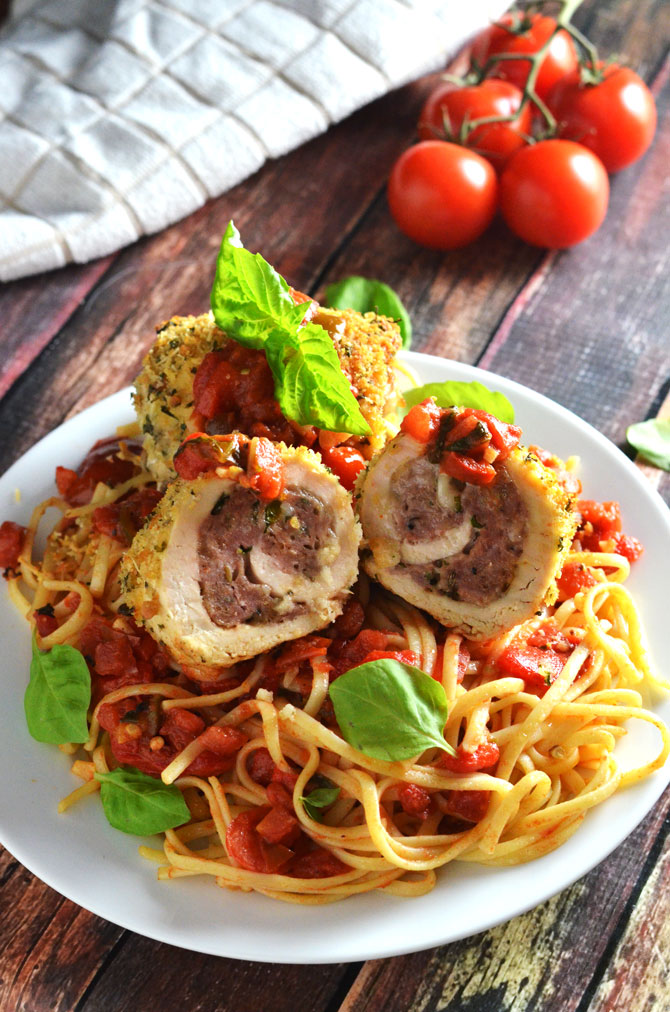 Sausage-Stuffed Chicken Rollatini with Roasted Red Pepper Tomato Sauce. Flavorful sausage is wrapped up in tender chicken breasts, baked, and topped with a tangy sauce for an easy and impressive weeknight dinner! | hostthetoast.com