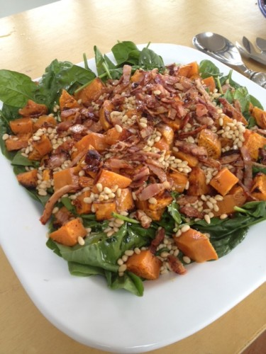 Roasted Kumera Salad on a bed of spinach, covered in pine nuts and crispy bacon