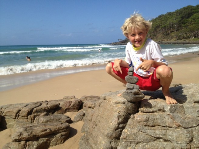 Alfie builds a rock sculpture on the beach at Tea Tree Bay