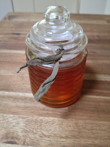 Sage infused honey in a bee hive jar