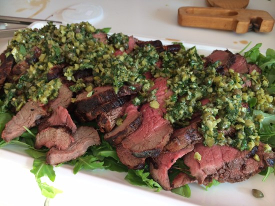 Eye fillet of beef on a bed of rocket with a dressing of cornichons, herbs and lemon juice