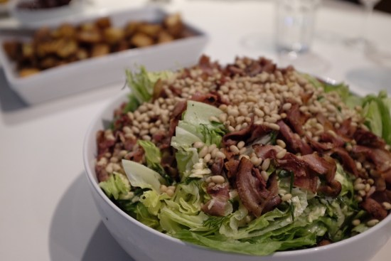 Salad topped with herbs, pine nuts and bacon