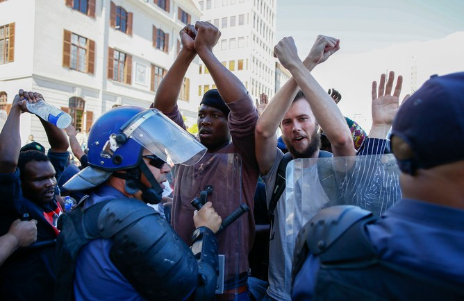 epa04987156 South African students clash with police during violent protests in the parliament precinct, Cape Town, South Africa, 21 October 2015. Protesters broke through the gates of parliamnet in an unprecedented violent protest that breached through the gates into parliament. Several students and police were injured in the clashes. Students are protesting against a proposed hike in tuition fees.  EPA/NIC BOTHMA