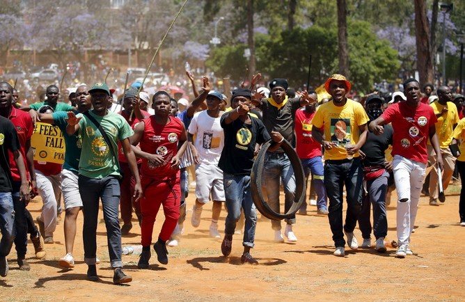 Demonstrators gesture at a photographer during a protest over planned increases in tuition fees outside the Union building in Pretoria, South Africa October 23, 2015. South African police fired stun grenades at students who lit fires outside President Jacob Zuma's offices following a week of protests, the first signs of the post-apartheid 'Born Free' generation flexing its muscle. REUTERS/Siphiwe Sibeko? - RTS5T06
