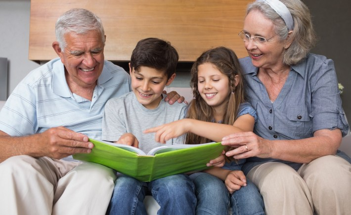 Happy grandparents and grandkids looking at album photo in the l