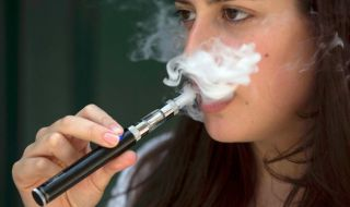 A woman smokes an electronic cigarette