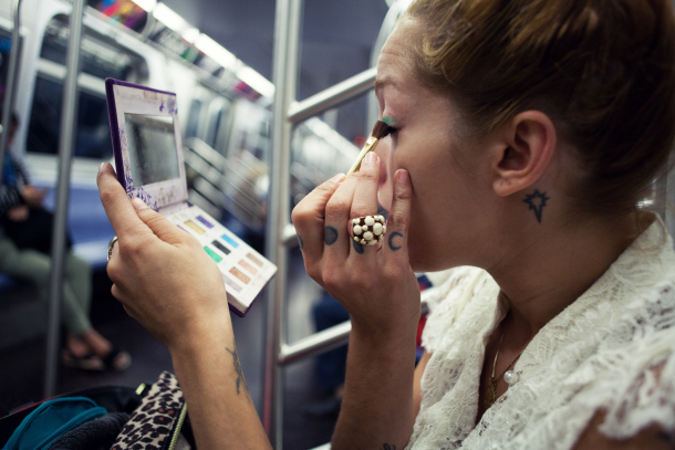 Young woman applying make-up on subway train  image source: stylecaster.com