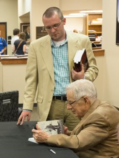 Dr. Lewis signs a book for Lewis Scholar, Garrett Best