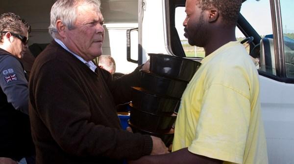 Patrocinio Mora entrega la cena a un inmigrante en la Nochevieja de 2012. (Julián Pérez)