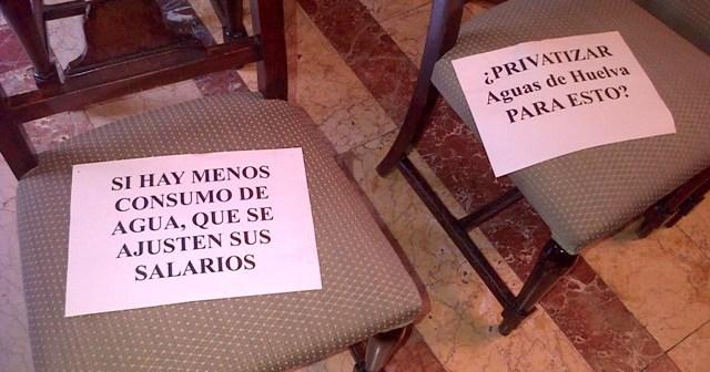 Dos panfletos de protesta contra la subida del agua en sillas del público del Pleno municipal.