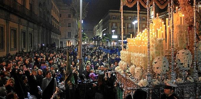 La Virgen de la Esperanza rodeada por una multitud en la carrera oficial durante el Miércoles Santo.