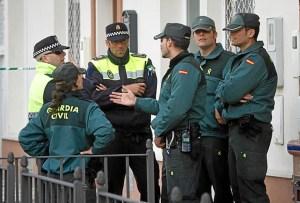 Efectivos de las fuerzas de seguridad conversan en la puerta del domicilio donde ocurrieron los asesinatos. (Julián Pérez)