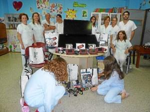 Personal del hospital junto a niños y algunas de las consolas.