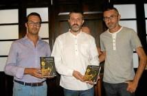 El delegado de Biblioteca  primero por la izquierda junto al autor y al presentador del mismo muestra un ejemplar de la novela.jpg