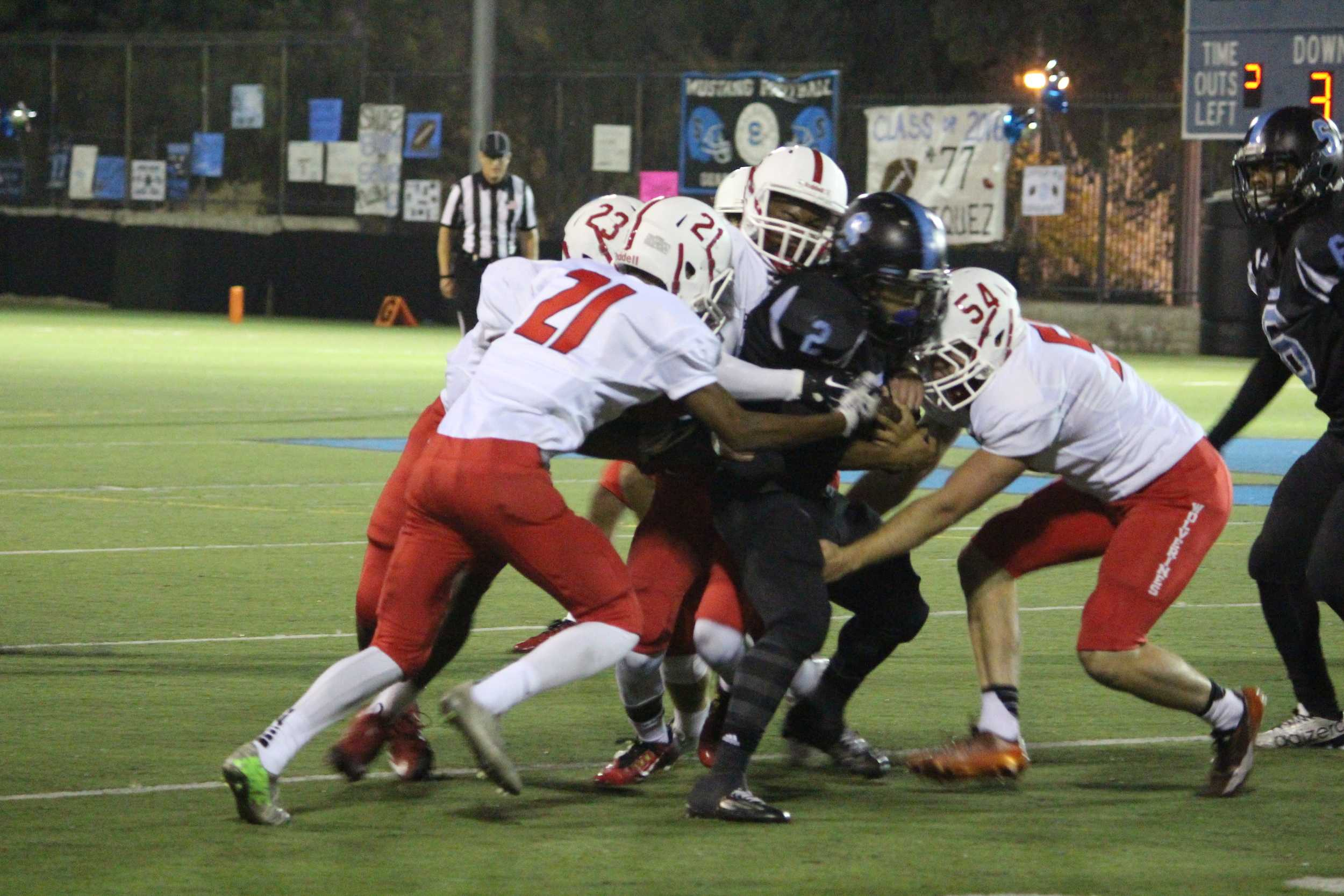 The Wolverines make a gang tackle on Salesian's Urael Blackshear '17 in the first quarter.