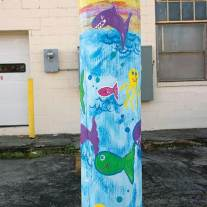 Against a cream-colored block building this cartoonish ocean-themed pole is innocent enough.