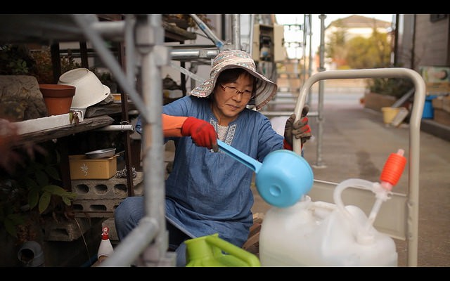 Tomoko Kobayashi filling a watering can from a spigot that her father made and passed onto her. Credit: Jake Price.