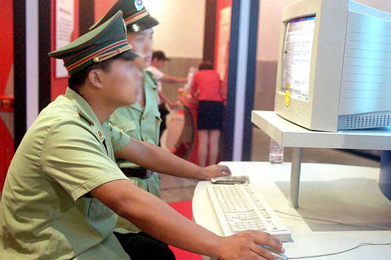 internet police in china File - computer users sit near a monitor display with a message from the  chinese police on the proper use of the internet at an internet cafe in.