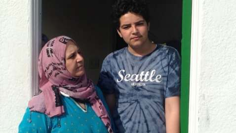 Fayzeh Ramadan and her 15-year-old son Mohamed Alsedawe in the doorway of their East Vancouver motel. Mohamed hasn't been able to start school because the family doesn't have a permanent home.