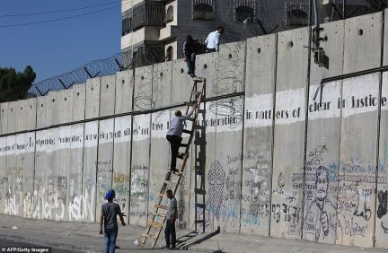 Not always effective: Palestinians were pictured in 2015 climbing over a section of Israel's separation wall to enter Jerusalem for Friday prayer in the al-Aqsa mosque compound, Islam's third-holiest site, during Ramadan