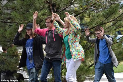 Students and teachers hold their hands in the air as they exit the scene of the shooting