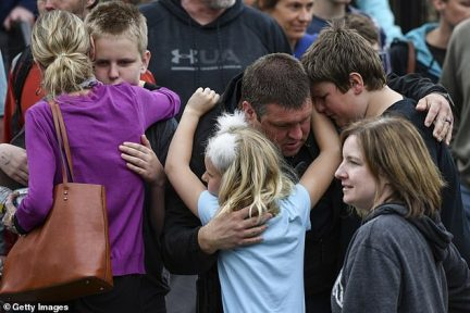 Parents embrace their children as they are reunited at a recreation center near the school